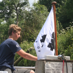 boy driving Hammerton's ferry with flag